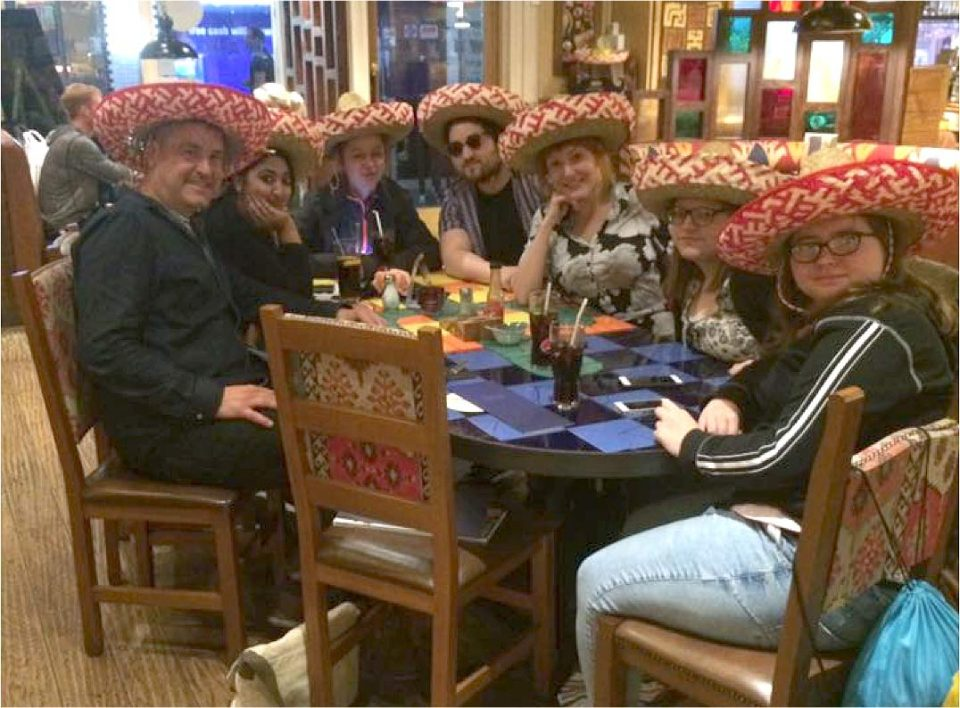 Team sat around a restaurant table wearing Mexican hats