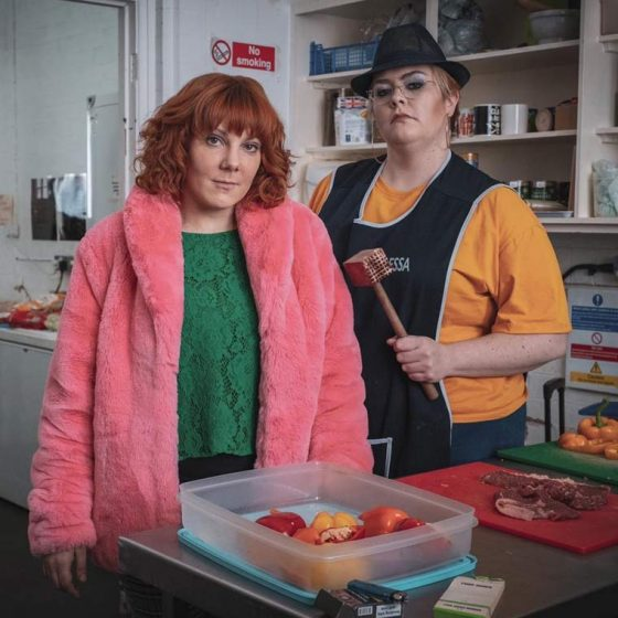 Sophie Willan and Jayde Adams stood in a butchers shop